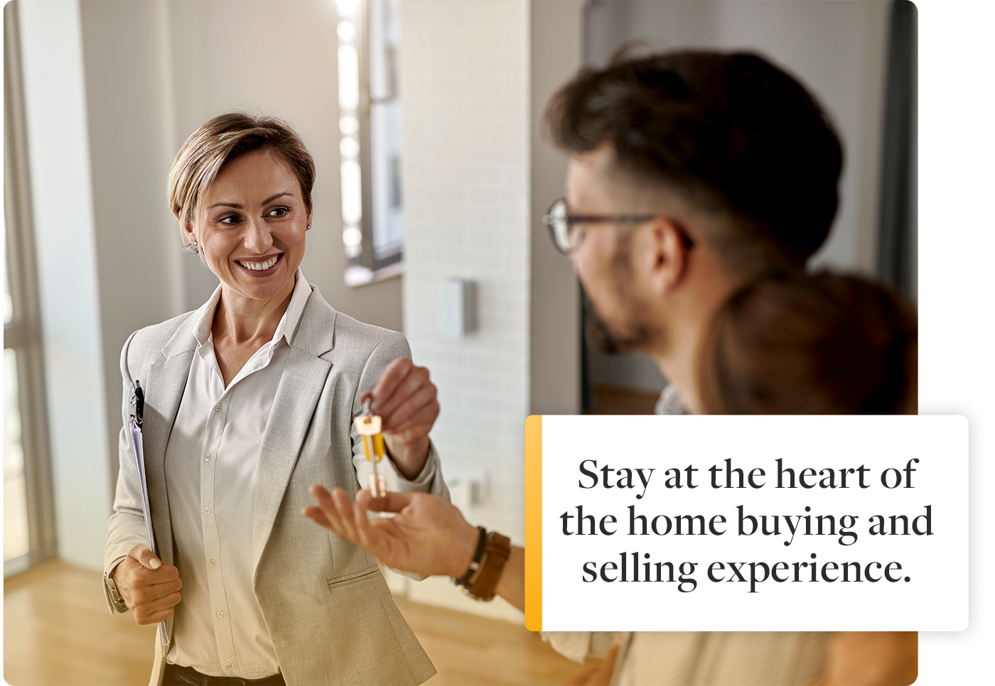 real estate agent in center of home buying experience with couple giving keys